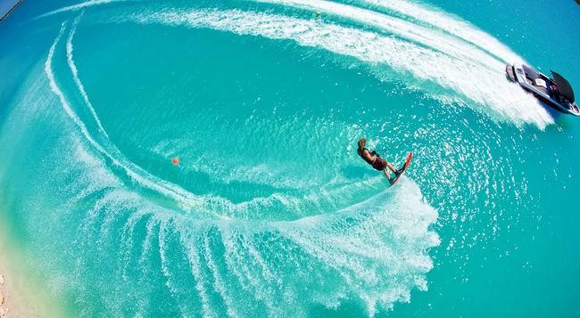 Лето, Калифорния, пляж. Неподалеку от берега на водных лыжах катается девушка
