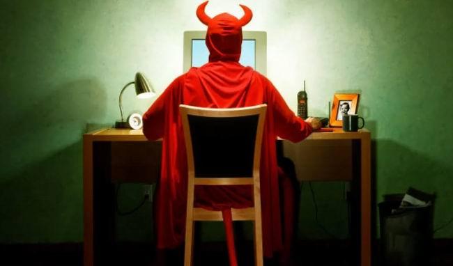Дьявол открывает ноутбук, щелкает мышкой и рассеянно смотрит в монитор