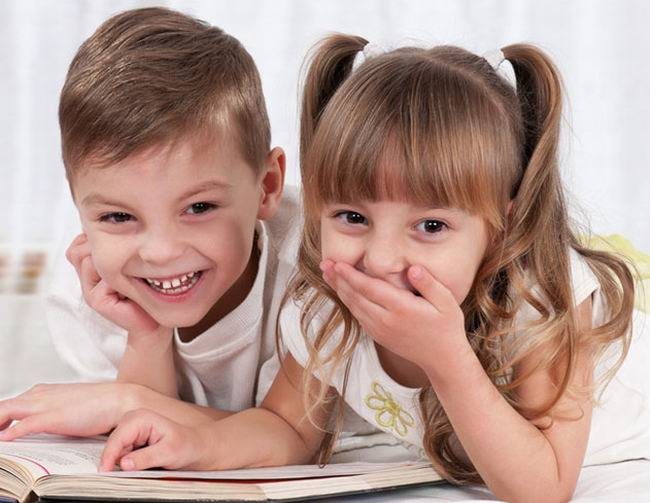 Маленькие мальчик и девочка рассматривают книгу Жизнь животных