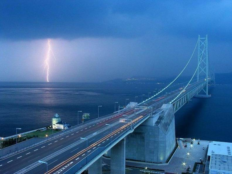Самый длинный висячий мост (определяется по длине основного пролета) расположен в Японии. Он соединяет город Кобе (остров Хонсю) и город Авадзи (одноименный остров). Центральный пролет этого моста в длину составляет 1991 метр, что, собственно и является рекордом. Общая длина моста - 3911 метров. Ах да, называется он Акаси-Кайкё.