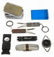 Средний этаж: передний слой: левый крайний<br> 58. Миниатюрная губка для чистки обуви<br> 59. Гильотинка для сигар<br>  60. Пластмассовая коробочка для пилюль<br> 61. Два сверхминиатюрных складных ножа<br> 62. Миниатюрный фонарь со светодиодом<br> 63. Флеш-диск емкостью 1 Г байт<br> 64. Флеш-диск емкостью 32 Г байт